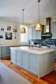 Island counter with marble worksurface and blue base units below brass pendant lamps in country-house kitchen