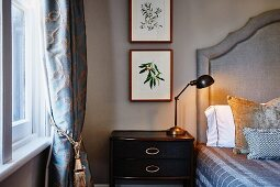 Retro table lamp on bedside table next to bed with upholstered headboard and framed pictures of plants on wall