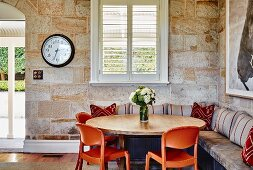 Orange plastic chairs around round wooden table and fitted corner bench against stone walls in corner of rustic living room