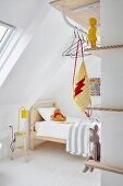 Wooden bed, clothes rail and narrow shelves in minimalist child's bedroom