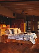Double bed with wooden frame and sun shining on headboard in bedroom in shades of brown