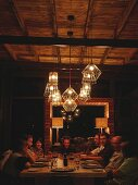 Guests around a table under lit wire pendant lamps in cosy atmosphere of safari lodge