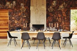 Black designer chairs around long solid wooden table in front of rustic stone wall in safari lodge