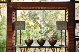 Metal bowls and table lamps arranged on narrow table in front of panoramic window with view of wild landscape