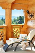 Modern outdoor lounger with white cushions on balcony of log cabin with view of idyllic landscape
