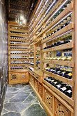 Pale wooden wine racks in narrow room with stone-clad wall and floor