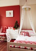 Romantically decorated bed with canopy and patchwork bedspread in girl's bedroom with red wall