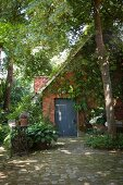 Climber-covered brick house in idyllic garden