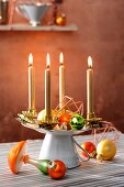 Advent wreath made from gold candles on stand made from upturned cup and saucer