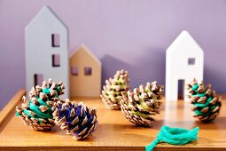 Pine cones wrapped with colourful thread and house-shaped ornaments