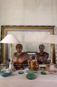 Arrangement of ceramic objects, antique table lamps with white lampshades, wooden busts and picture frames