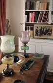 Vintage glass paraffin lamps on antique desk in front of white bookcase