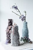 Dried flowers in vases in knitted and crocheted covers