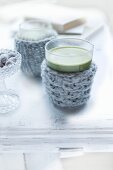 Glasses of green matcha tea in knitted glass cosies