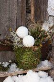 Zweige und Weihnachtskugeln in mit Moos umwickeltem Pflanztopf