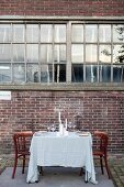Rustic set table in front of industrial façade