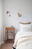 Simple wooden bedside table next to bed below bird motifs on wall and wall-mounted lamp