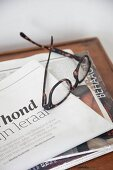 Reading glasses lying on newspaper