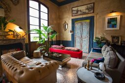 Yellow-painted, eclectic Mediterranean interior with various seats around coffee table