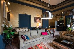 Green sofa with colourful scatter cushions in eclectic living room in period apartment with historical ambiance