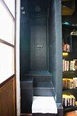 Schmaler Duschbereich mit dunkelgrauen Fliesen auf erhöhter Ebene, seitlich offenes beleuchtetes Bücherregal