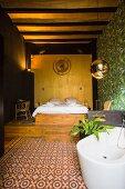 Free-standing bathtub on patterned tiled floor, bed on wooden platform in background