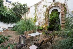 Begrünter mediterraner Innenhof mit Vintage-Brunnen und Outdoormöbeln