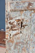 Vintage wooden door with peeling paint and wrought iron fittings