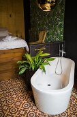 Modern free-standing white bathtub on ornamental tiled floor against half-height wall; bed in background