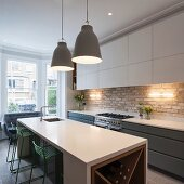 Fitted kitchen with white wall units, pendant lamps above island counter and green bar stools