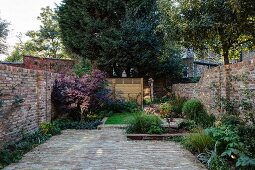 Well-tended garden of terrace house with paved area, herbaceous borders and brick walls