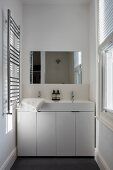 Twin washstand with white base unit and shiny towel rail in narrow bathroom with window