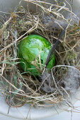 Green Easter eggs in hay nest