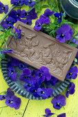 Eine Tafel Schokolade mit Ostermotiv, umgeben von Hornveilchen