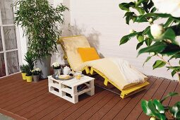 DIY side table and lounger made from pallets on terrace