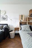 Bett mit gestapelten Regalelementen als Betthaupt