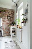 Schmale Küche mit Backsteinwand und Servierwagen