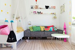 Coffee table, grey marled sofa, toys on white floating shelves and bed with canopy in girl's bedroom