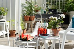 Watermelon, drinks and potted geranium on set of white side tables on terrace