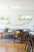 Wohnraum mit Holzsessel und passendem Edelholztisch, Wanddekoration mit Wimpelgirlande unter Oberlichtfenstern