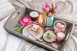 Romantically arranged breakfast and gifts on tray