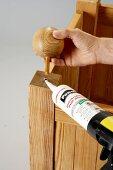 Sticking an ornamental ball onto a DIY wooden planter