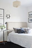Bed with fabric headboard with ornamental studs, bedside lamp on bistro table and black and white framed pictures
