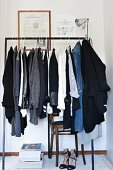 Woman's clothing hung on minimalist metal clothes rail above blac high heels in corner
