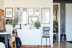 Workspace in front of gallery of pictures above white sideboard in retro interior