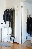 Black leather jacket hung on full-length mirror in hallway next to open interior door