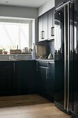 Black, L-shaped kitchen units and glossy fridge-freezer