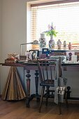 Antique wooden chair at cluttered desk with turned legs below window with vases on sill