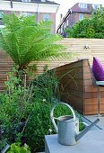Zinc watering can on terrace in front of wooden screen and bed of green plants