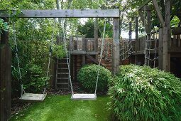 Wooden swings and climbing frame in summery garden